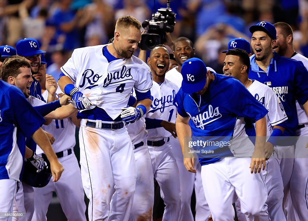 Alex Gordon #4 of the Kansas City Royals is congratulated at home plate by teammates after hitting a game-winning 2-run home run against the Minnesota Twins in the bottom of the 9th inning to win the game 2-1 at Kauffman Stadium on August 26, 2014 in Kansas City, Missouri.