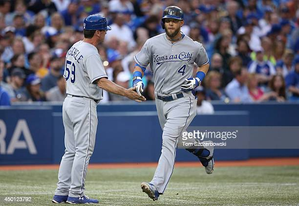 Alex Gordon of the Kansas City Royals is congratulated by third base coach Mike Jirschele after hitting a tworun home run in the fourth inning during...