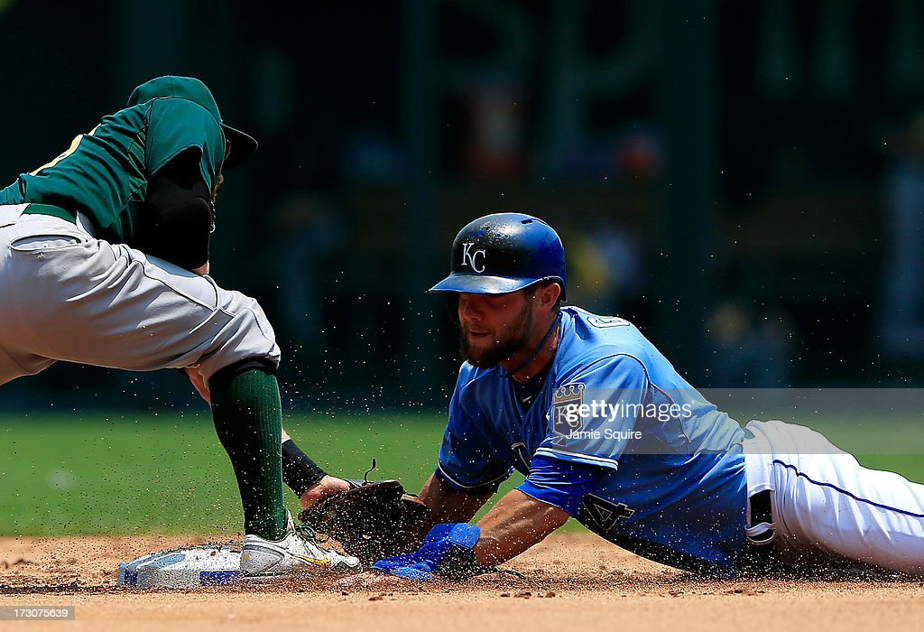Alex Gordon #4 of the Kansas City Royals is safe as Eric Sogard #28 of the Oakland Athletics is late applying the tag during the game at Kauffman Stadium on July 6, 2013 in Kansas City, Missouri.