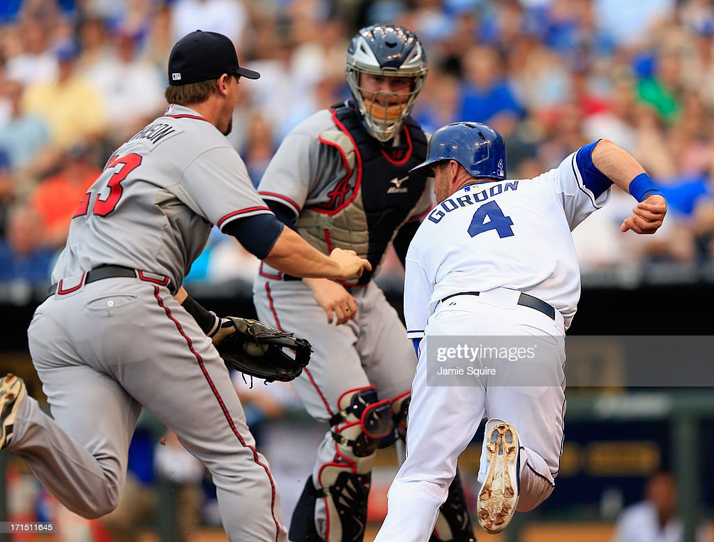 Alex Gordon of the Kansas City Royals is tagged out in a rundown between thirdbaseman Chris Johnson and catcher Brian McCann of the Atlanta Braves...