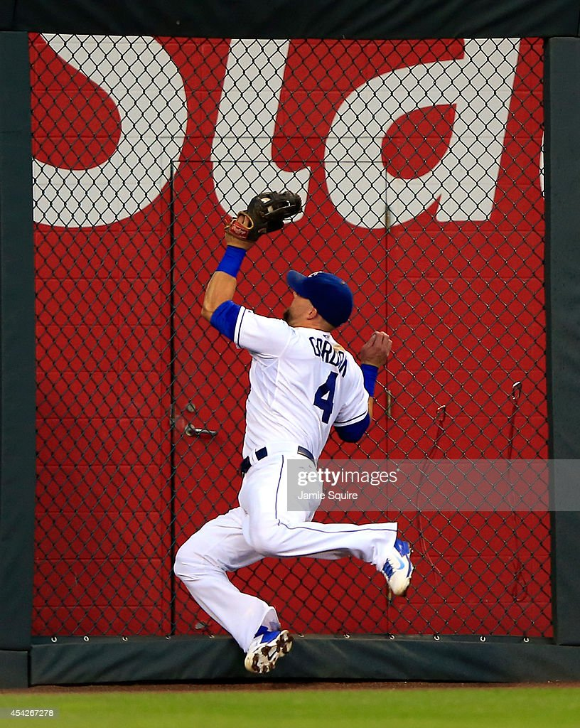 Alex Gordon #4 of the Kansas City Royals makes a leaping catch against the left field fence to rob Kurt Suzuki #8 of the Minnesota Twins of a hit during the 3rd inning of the game at Kauffman Stadium on August 27, 2014 in Kansas City, Missouri.