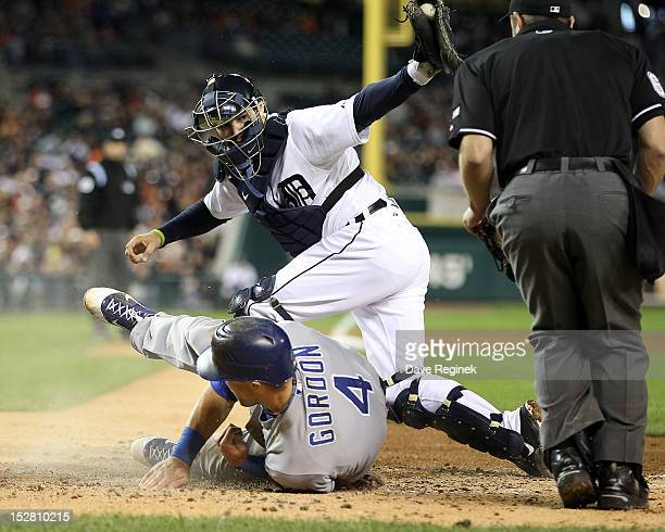 Alex Gordon of the Kansas City Royals slides home head first to score and beat the tag of Alex Avila of the Detroit Tigers during a MLB game at...