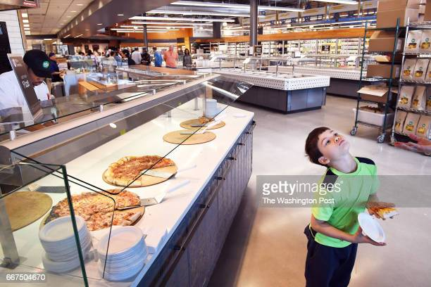 Alex Grob 7 samples a slice of pizza during an event at the Whole Foods Market at Riverdale Park Station on Sunday April 09 2017 in Riverdale Park MD...