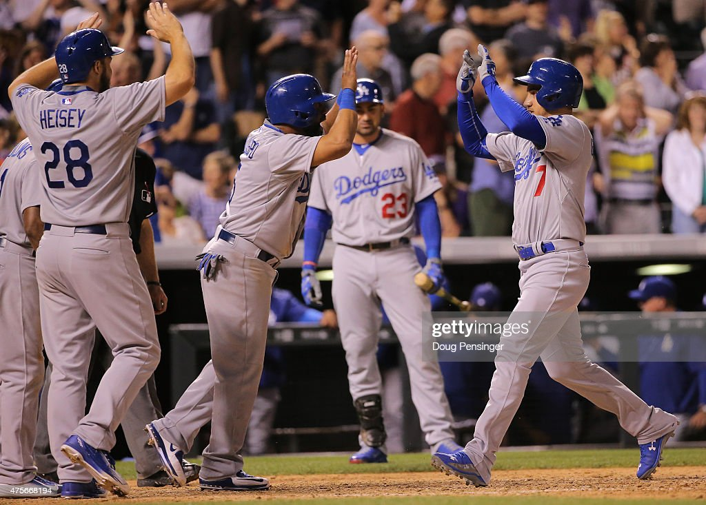 Alex Guerrero #7 of the Los Angeles Dodgers celebrates his game winning grand slam off of <a gi-track='captionPersonalityLinkClicked' href=/galleries/search?phrase=Rafael+Betancourt&family=editorial&specificpeople=224728 ng-click='$event.stopPropagation()'>Rafael Betancourt</a> #63 of the Colorado Rockies with <a gi-track='captionPersonalityLinkClicked' href=/galleries/search?phrase=Alberto+Callaspo&family=editorial&specificpeople=835933 ng-click='$event.stopPropagation()'>Alberto Callaspo</a> #5, <a gi-track='captionPersonalityLinkClicked' href=/galleries/search?phrase=Chris+Heisey&family=editorial&specificpeople=5971787 ng-click='$event.stopPropagation()'>Chris Heisey</a> #28 and <a gi-track='captionPersonalityLinkClicked' href=/galleries/search?phrase=Jimmy+Rollins&family=editorial&specificpeople=204478 ng-click='$event.stopPropagation()'>Jimmy Rollins</a> #11 of the Los Angeles Dodgers in the ninth inning during game two of a double header at Coors Field on June 2, 2015 in Denver, Colorado. The Dodgers defeated the Rockies 9-8.