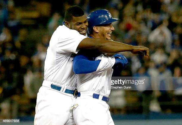 Alex Guerrero of the Los Angeles Dodgers is hugged by Yasiel Puig after Guerrero's game winning walk off RBI single in the 10th inning against the...
