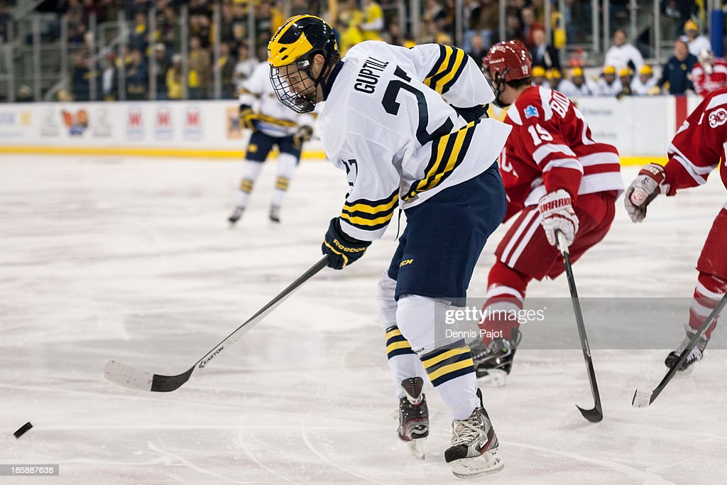 Alex Guptill #27 of the Michigan Wolverines skates against Robbie Baillargeon #19 of the Boston University Terriers on October 25, 2013 at Yost Ice Arena in Ann Arbor, Michigan.