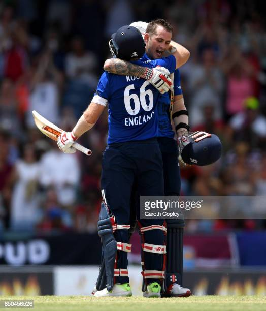 Alex Hales of England celebrates with Joe Root after reaching his century during the 3rd One Day International between the West Indies and England at...
