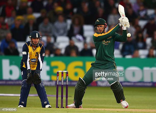 Alex Hales of Nottinghamshire hits the ball towards the boundary as Tim Ambrose of Warwickshire looks on during the NatWest T20 Blast match between...