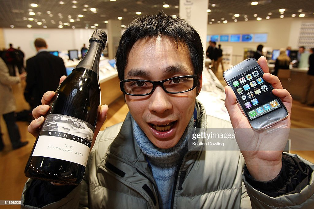 Alex Ho, a student from Hong Kong, celebrates after receiving a bottle of wine for being the first customer to purchase the new Apple iPhone 3G after waiting from 10pm the night before at the Bourke Street T Life store on July 11, 2008 in Melbourne, Australia. The iPhone 3G is a multimedia mobile device with a touch screen that enables e-mail and web browsing.