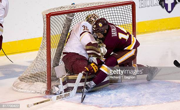 Alex Iafallo of the Minnesota Duluth Bulldogs crashes into Thatcher Demko of the Boston College Eagles during the NCAA Division I Men's Ice Hockey...