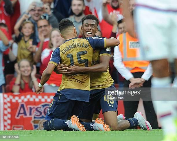 Alex Iwobi celebrates scoring a goal for Arsenal with Alex OxladeChamberlain during the match between Arsenal and Olympic Lyon at Emirates Stadium on...