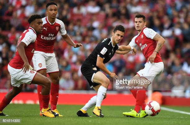 Alex Iwobi Cohen Bramall and Granit Xhaka of Arsenal challenge Sebastien Corchia of Seville during the Emirates Cup match between Arsenal and Seville...
