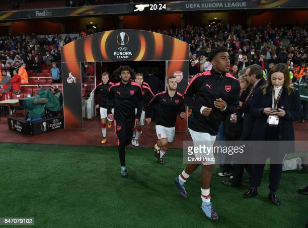 Alex Iwobi Mohamed Elneny and Jack Wilshere of Arsenal run out to warm up before the UEFA Europa League group H match between Arsenal FC and 1 FC...