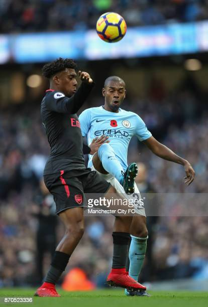 Alex Iwobi of Arsenal and Fernandinho of Manchester City battle for possession during the Premier League match between Manchester City and Arsenal at...