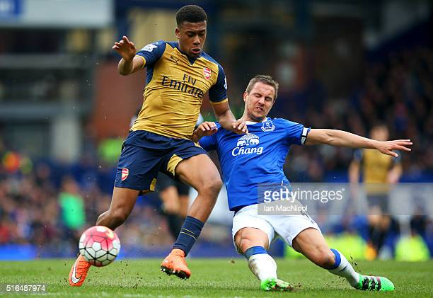 Alex Iwobi of Arsenal and Phil Jagielka of Everton compete for the ball during the Barclays Premier League match between Everton and Arsenal at...