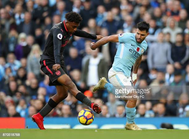 Alex Iwobi of Arsenal and Sergio Aguero of Manchester City battle for possession during the Premier League match between Manchester City and Arsenal...