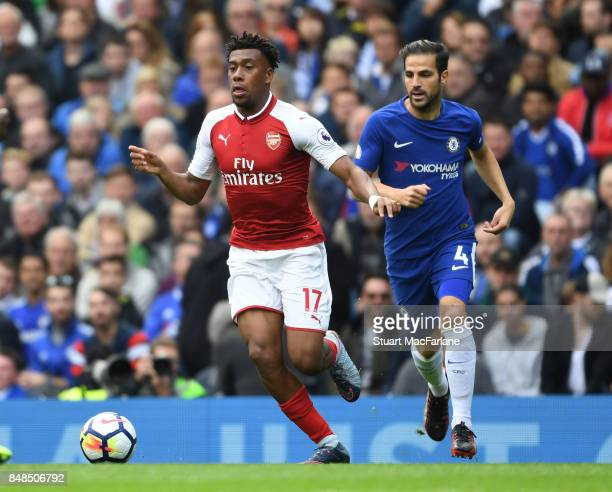 Alex Iwobi of Arsenal breaks past Cesc Fabregas of Chelsea during the Premier League match between Chelsea and Arsenal at Stamford Bridge on...