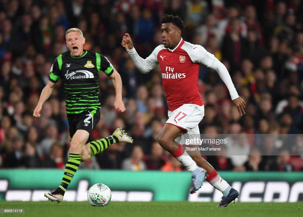Alex Iwobi of Arsenal breaks past Craig Alcock of Doncaster during the Carabao Cup Third Round match between Arsenal and Doncaster Rovers at Emirates Stadium on September 19, 2017 in London, England.