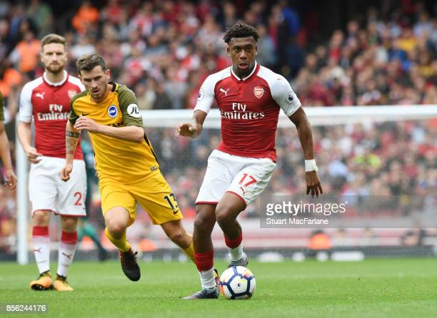 Alex Iwobi of Arsenal breaks past Pascal Gross of Brighton during the Premier League match between Arsenal and Brighton and Hove Albion at Emirates...