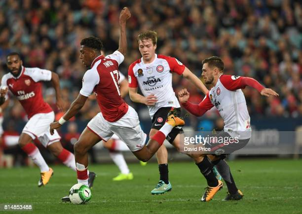Alex Iwobi of Arsenal bursts past Jacob Melling and Josh Risdon of Western Sydney during the match between the Western Sydney Wanderers and Arsenal...
