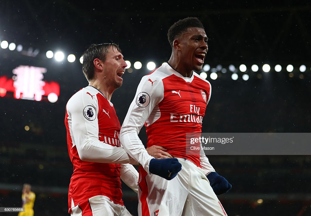 Alex Iwobi of Arsenal celebrates with teammate Nacho Monreal (L) after scoring his team's second goal during the Premier League match between Arsenal and Crystal Palace at the Emirates Stadium on January 1, 2017 in London, England.