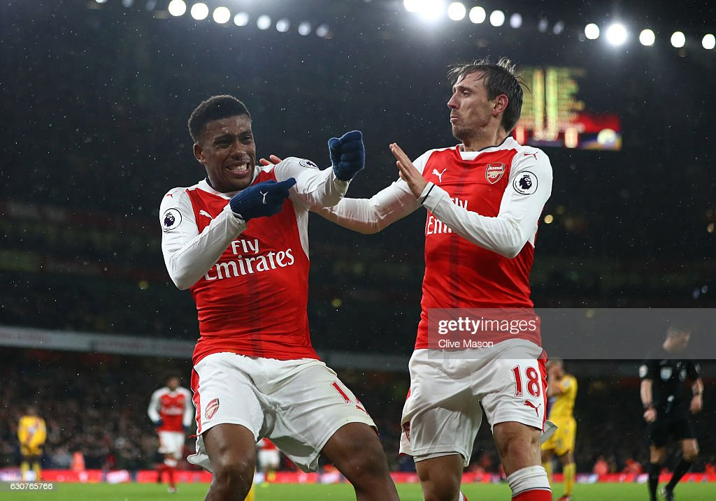 Alex Iwobi of Arsenal celebrates with teammate Nacho Monreal (R) after scoring his team's second goal during the Premier League match between Arsenal and Crystal Palace at the Emirates Stadium on January 1, 2017 in London, England.