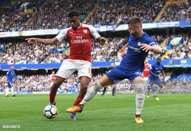 Alex Iwobi of Arsenal challenged by Gary Cahill of Chelsea during the Premier League match between Chelsea and Arsenal at Stamford Bridge on...