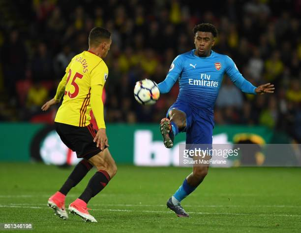 Alex Iwobi of Arsenal challenged by Richarlison of Watford during the Premier League match between Watford and Arsenal at Vicarage Road on October 14...