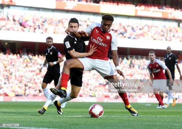 Alex Iwobi of Arsenal challenged by Sebastien Corchia of Seville during the Emirates Cup match between Arsenal and Seville at Emirates Stadium on...