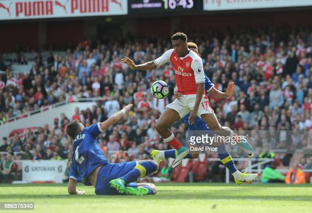 Alex Iwobi of Arsenal controls the ball under pressure from Morgan Schneiderlin and Mason Holgate of Everton during the Premier League match between...
