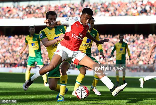 Alex Iwobi of Arsenal controls the ball under pressure of Jonathan Howson of Norwich City during the Barclays Premier League match between Arsenal...