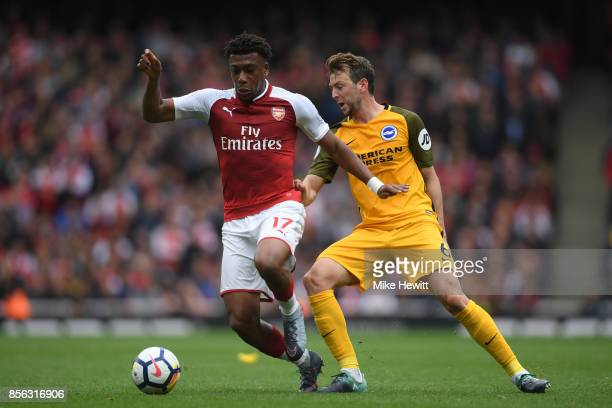 Alex Iwobi of Arsenal is challenged by Dale Stephens of Brighton during the Premier League match between Arsenal and Brighton and Hove Albion at...
