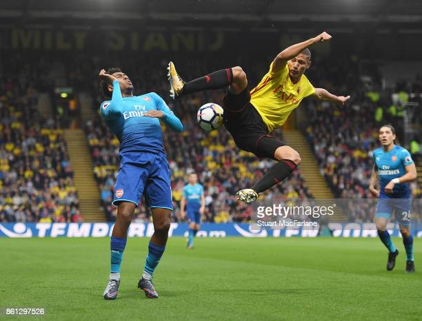 Alex Iwobi of Arsenal is challenged by Richarlison of Watford during the Premier League match between Watford and Arsenal at Vicarage Road on October...