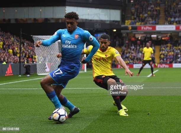 Alex Iwobi of Arsenal is closed down by Adrian Mariappa of Watford during the Premier League match between Watford and Arsenal at Vicarage Road on...