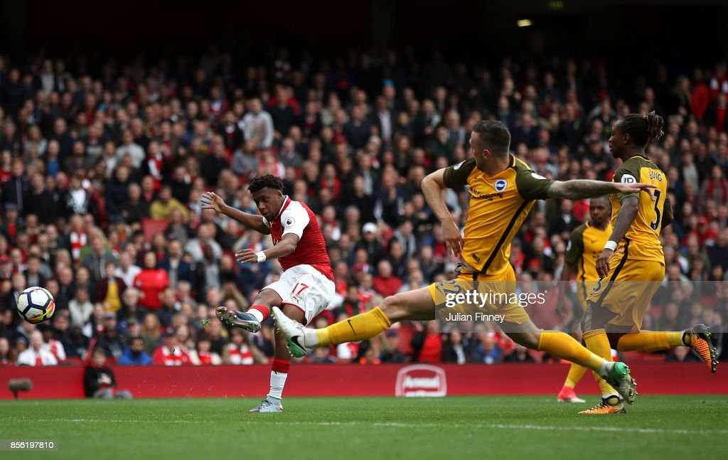 Alex Iwobi of Arsenal scores his sides second goal as Shane Duffy of Brighton and Hove Albion attempts to block during the Premier League match between Arsenal and Brighton and Hove Albion at Emirates Stadium on October 1, 2017 in London, England.