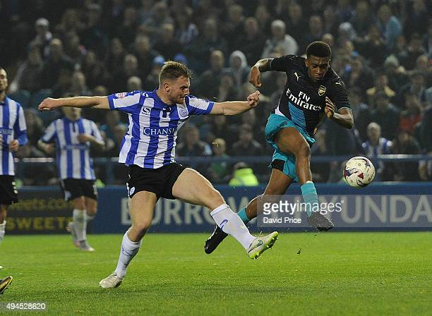 Alex Iwobi of Arsenal shoots under pressure from Tom Lees of Sheffield Wednesday during the Capital One Cup 4th Round match between Sheffield...