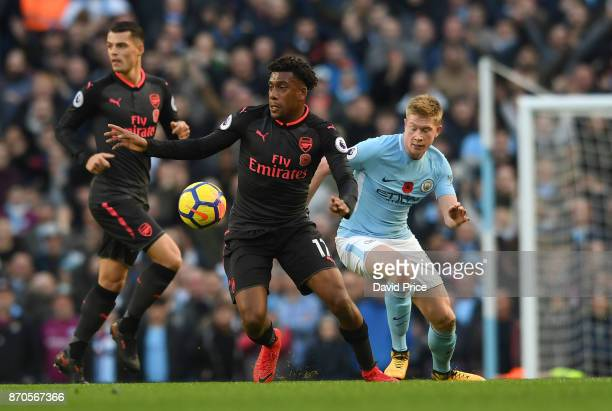 Alex Iwobi of Arsenal takes on Kevin De Bruyne of Man City during the Premier League match between Manchester City and Arsenal at Etihad Stadium on...