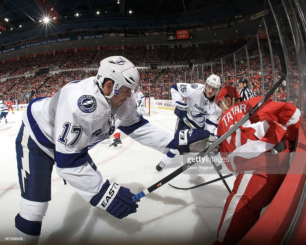 Alex Killorn #17 and <a gi-track='captionPersonalityLinkClicked' href=/galleries/search?phrase=Matt+Carle&family=editorial&specificpeople=582495 ng-click='$event.stopPropagation()'>Matt Carle</a> #25 of the Tampa Bay Lightning battle for the puck with <a gi-track='captionPersonalityLinkClicked' href=/galleries/search?phrase=Tomas+Tatar&family=editorial&specificpeople=5652303 ng-click='$event.stopPropagation()'>Tomas Tatar</a> #21 of the Detroit Red Wings in the corner during an NHL game at Joe Louis Arena on November 9, 2013 in Detroit, Michigan.