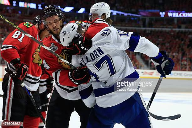 Alex Killorn of the Tampa Bay Lightning and Niklas Hjalmarsson of the Chicago Blackhawks get involved after the whistle in the first period during...