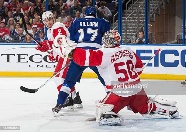 Alex Killorn of the Tampa Bay Lightning attempts to block the view of goalie Jonas Gustavsson of the Detroit Red Wings while battling with Brendan...