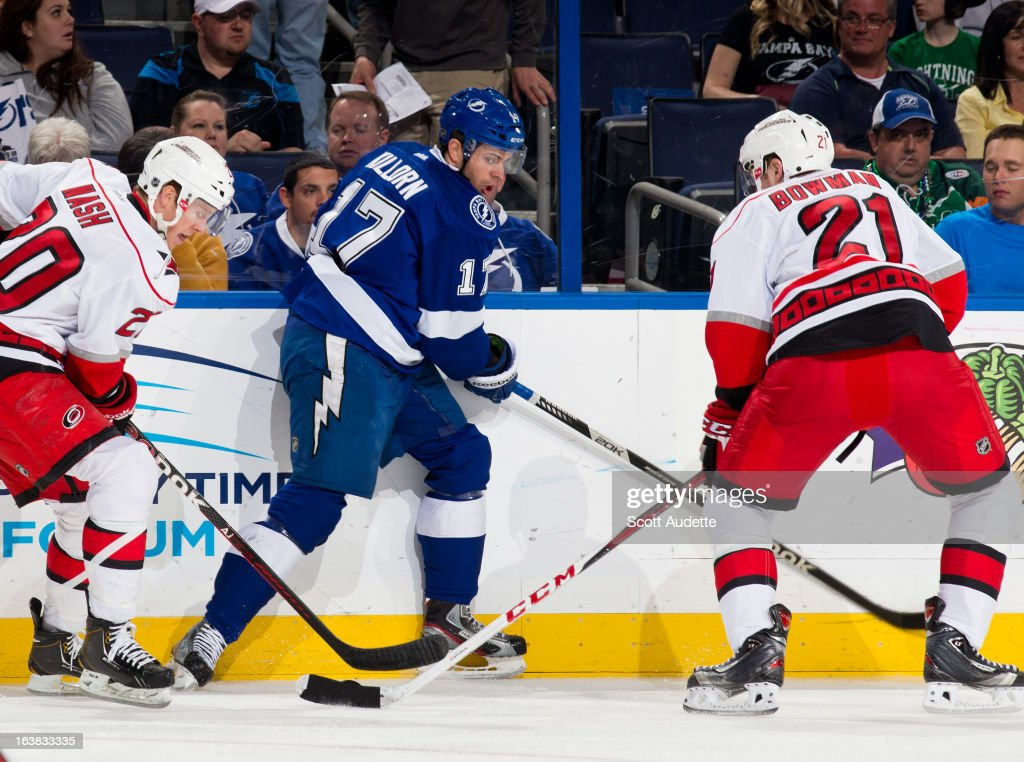 Alex Killorn #17 of the Tampa Bay Lightning battles for the puck along the boards with Riley Nash #20 and <a gi-track='captionPersonalityLinkClicked' href=/galleries/search?phrase=Drayson+Bowman&family=editorial&specificpeople=4111563 ng-click='$event.stopPropagation()'>Drayson Bowman</a> #21 of the Carolina Hurricanes during the first period of the game at the Tampa Bay Times Forum on March 16, 2013 in Tampa, Florida.