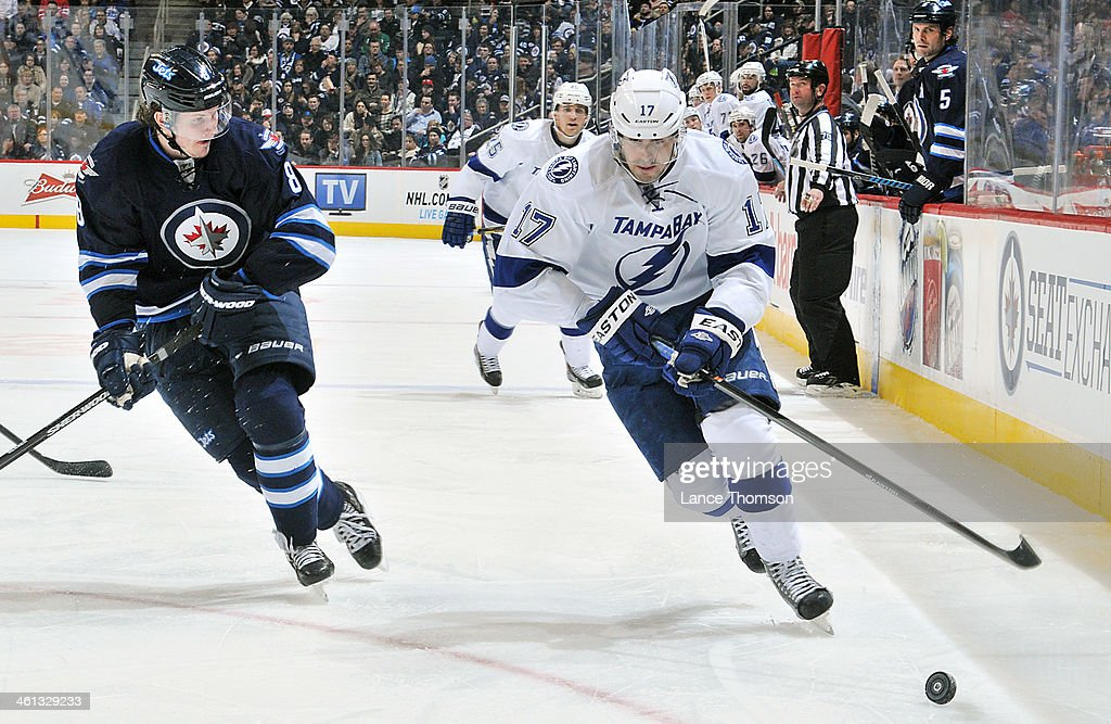 Alex Killorn #17 of the Tampa Bay Lightning follows the puck down the ice as Jacob Trouba #8 of the Winnipeg Jets gives chase during third period action at the MTS Centre on January 7, 2014 in Winnipeg, Manitoba, Canada.