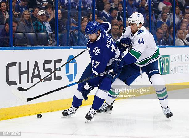 Alex Killorn of the Tampa Bay Lightning skates against Erik Gudbranson of the Vancouver Canucks during the first period at Amalie Arena on December 8...