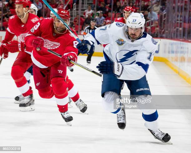 Alex Killorn of the Tampa Bay Lightning skates up ice next to Trevor Daley of the Detroit Red Wings during an NHL game at Little Caesars Arena on...