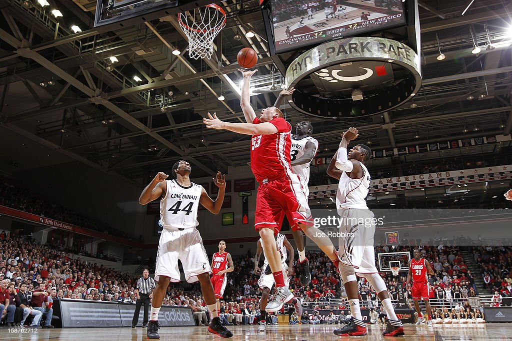 Alex Kirk #53 of the New Mexico Lobos goes to the basket against Cheikh Mbodj #13 and JaQuon Parker #44 of the Cincinnati Bearcats during the game at Fifth Third Arena on December 27, 2012 in Cincinnati, Ohio. New Mexico won 55-54.