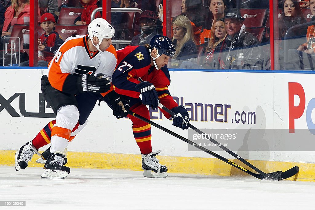 Alex Kovalev #27 of the Florida Panthers digs the puck out from the boards against Mike Knuble #09 of the Philadelphia Flyers at the BB&T Center on January 26, 2013 in Sunrise, Florida.
