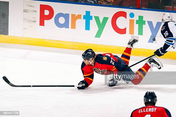 Alex Kovalev of the Florida Panthers is tripped by Andrew Ladd of the Winnipeg Jets at the BBT Center on January 31 2013 in Sunrise Florida