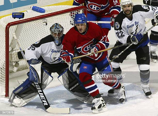 Alex Kovalev of the Montreal Canadiens battles for crease position against Dan Boyle of the Tampa Bay Lightning in front of Lightning goalie Nikolai...