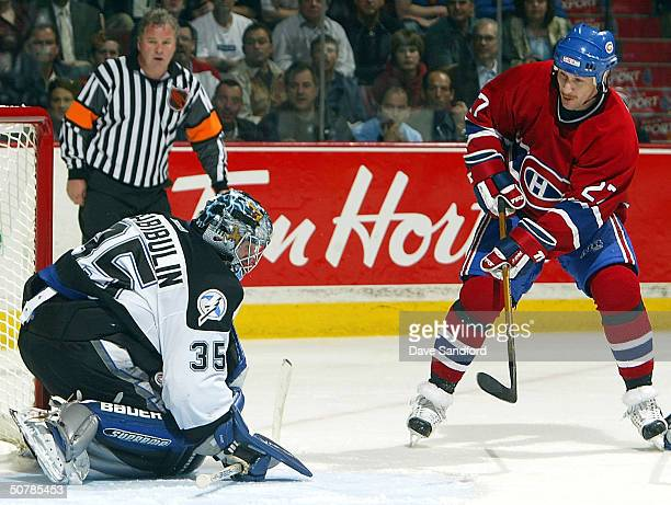 Alex Kovalev of the Montreal Canadiens has his shot stopped as Nikolai Khabiboulin of the Tampa Bay Lightning squeezes the puck between his arm and...