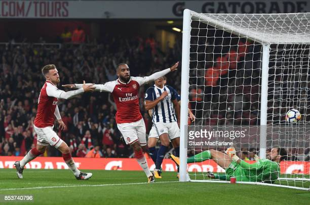 Alex Lacazette of Arsenal celebrates with teammate Aaron Ramsey after scoring the opening goal during the Premier League match between Arsenal and...